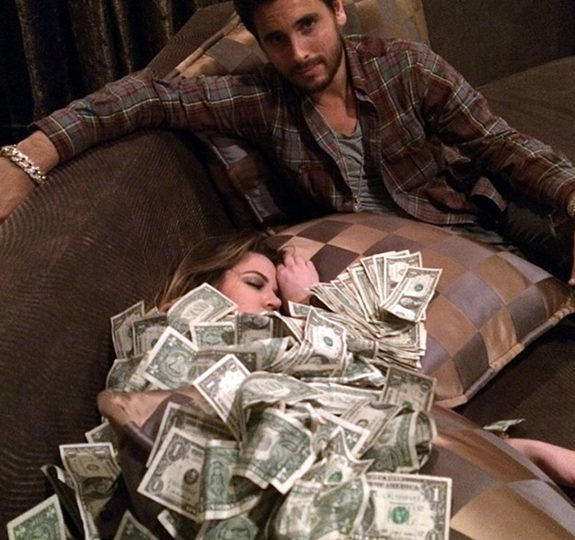 Oh look, Scott Disick covered one of the Kardashians in money. Isn't he swell?